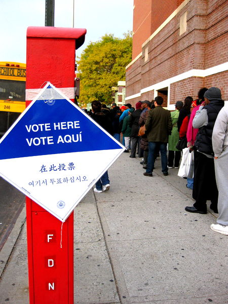 "People waiting to vote stand in a line next to a brick building. A sign that reads ""Vote Here"" in several languages is posted to the left of the waiting voters."