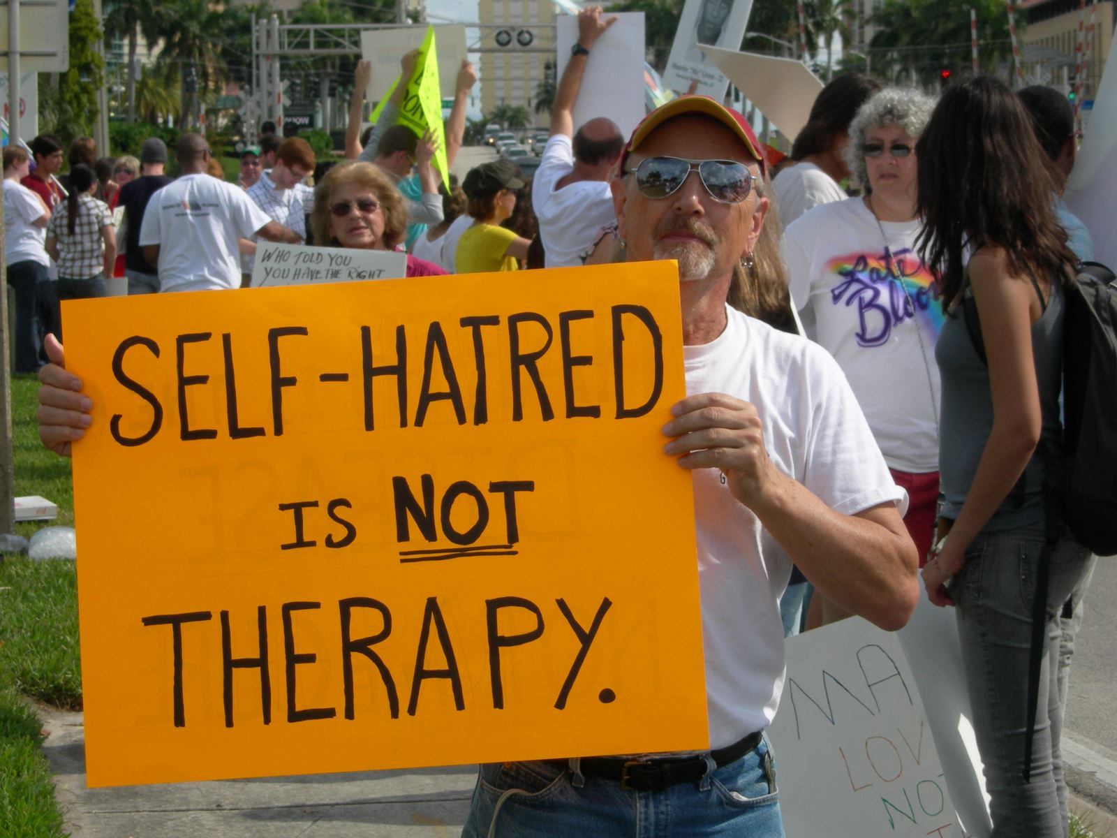 "Man wearing a cap, sunglasses, a white t-shirt and jeans stands in a crowd and holds a sign that reads, ""Self-Hatred is NOT Therapy""."
