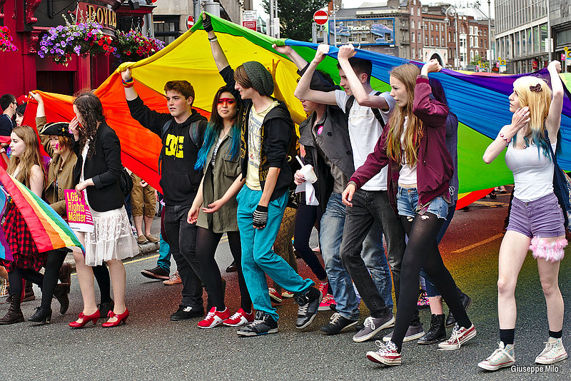 A group of young people march down a street holding a giant rainbow flag over their heads.