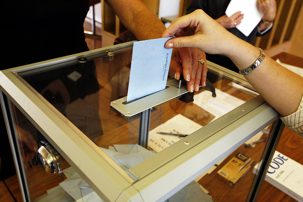 A person drops a ballot into a slot on the top of a clear box
