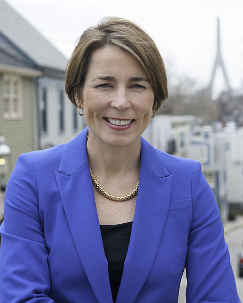 Photograph of Attorney General Maura Healey. She is standing outdoors near several houses, with the Zakim bridge in the background.