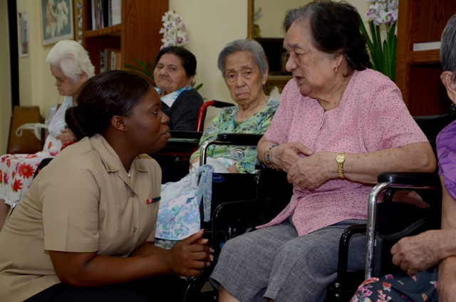 Nurse kneels by an older woman sitting in a wheelchair