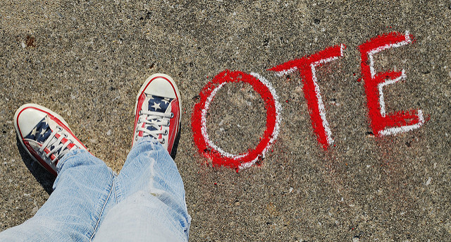 A pair of feet in red, white and blue sneakers form a V in the word VOTE, written in white chalk on a sidewalk.
