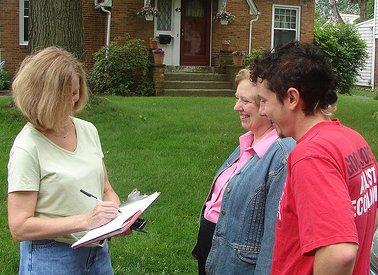 A canvasser talking with two people in front of a house