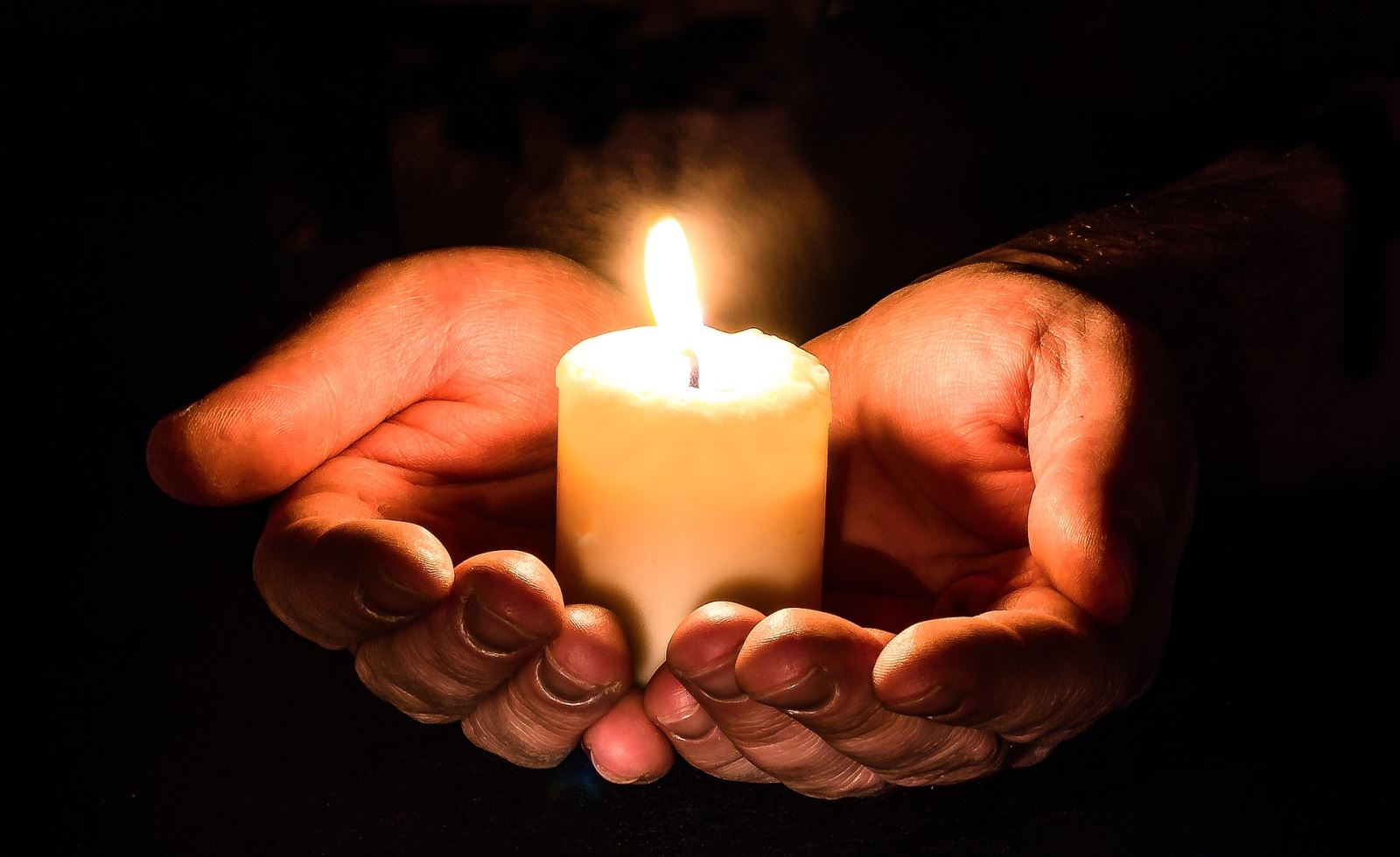 Two hands hold a small, lit candle in the darkness.